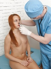 Scared redhead with a dental gag and a speculum