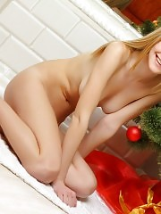 Busty teen blonde with a gorgeous body strips down by the Christmas tree and poses naked.