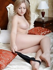 Excellent beauty with splendid tits stripping panties and showing shaved pussy on the bed.