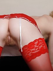 Seductive curly blonde with a fresh tight body posing in red stockings and stripping nude.