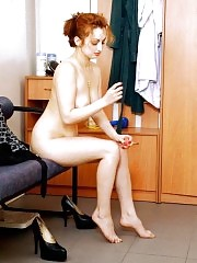 Hot redhead babe dressing in front of the mirror